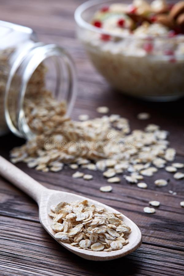 Composition with bowl of oatmeal porrige and dry oatmeal in glassware on vintage wooden table, selective focus stock photos