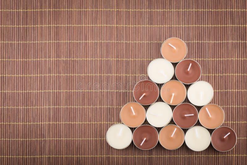 Composition triangulaire des bougies de lumière de thé sur un placemat en bambou images libres de droits
