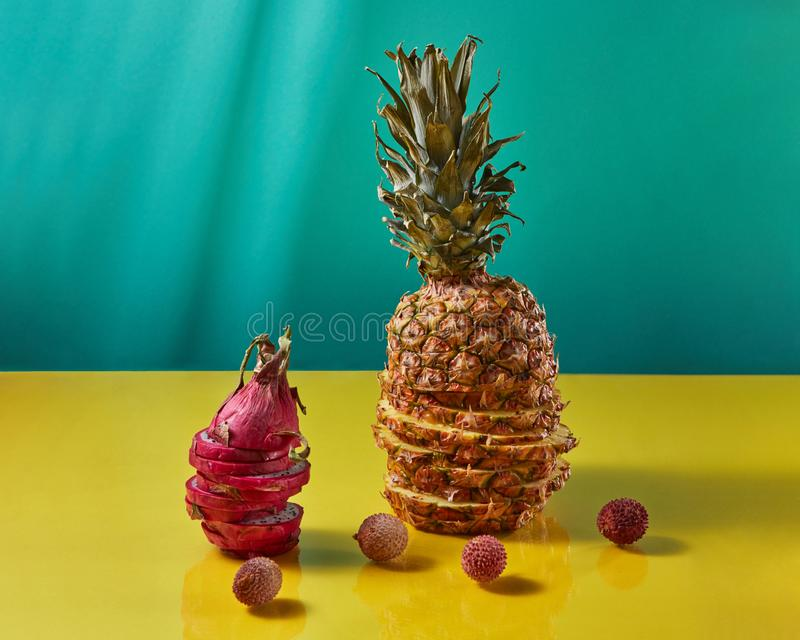 Tropical Pineapple fruit single whole and dragon fruit, pitaya made up of sliceson and litchi fruits on a duotone yellow royalty free stock photo