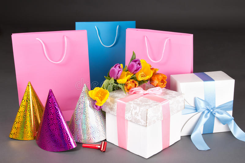 Composition of tulips, gift boxes and birtday hats over grey. Composition of tulip flowers, gift boxes and birtday hats over grey stock images