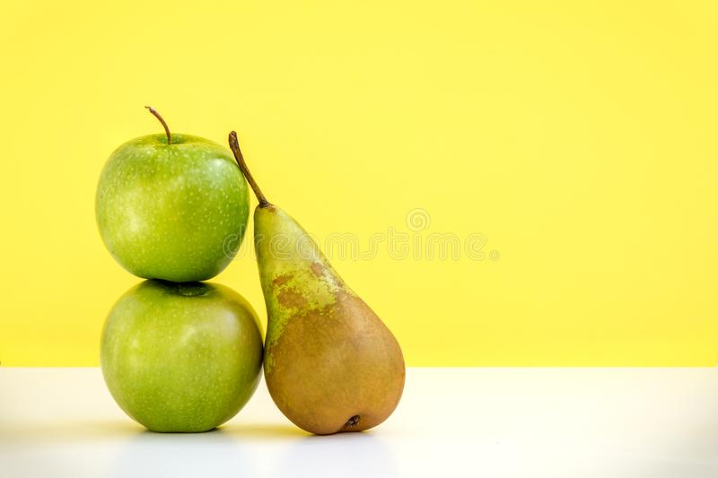 The composition of two fresh green apples and one long pear on yellow background stock image