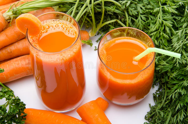 Composition with two glasses of carrot juice and carrots stock image