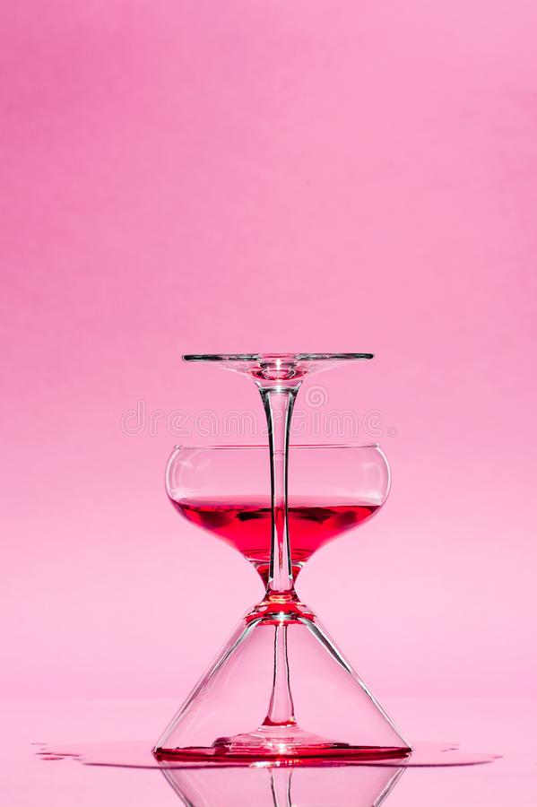 Composition from two glasses with drinks on a pastel pink background. Creative conceptual photography royalty free stock images