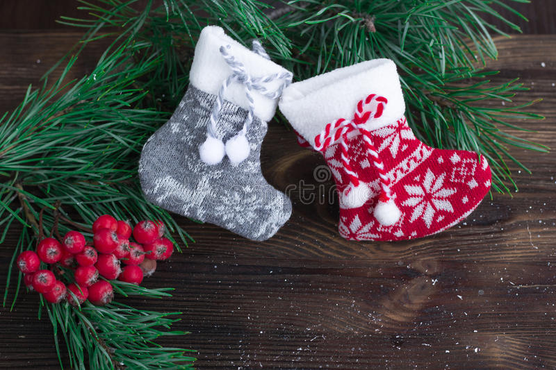 Composition of two knitted socks, berries and christmas tree bra stock photo