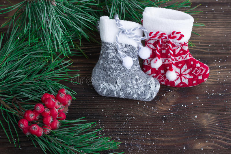 Composition of two knitted socks, rowan and xmas tree branches stock photos