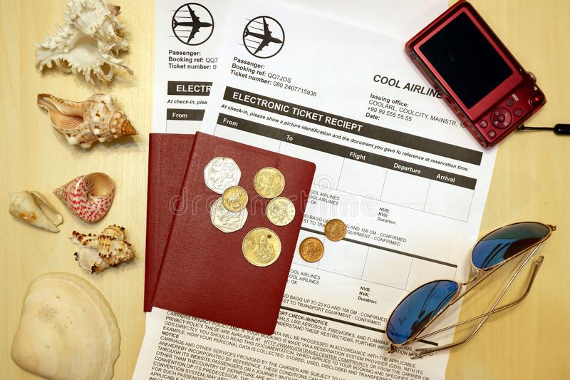 Composition from two passports with air tickets, compact camera, sunglasses, sea shells and foreign coins royalty free stock photos