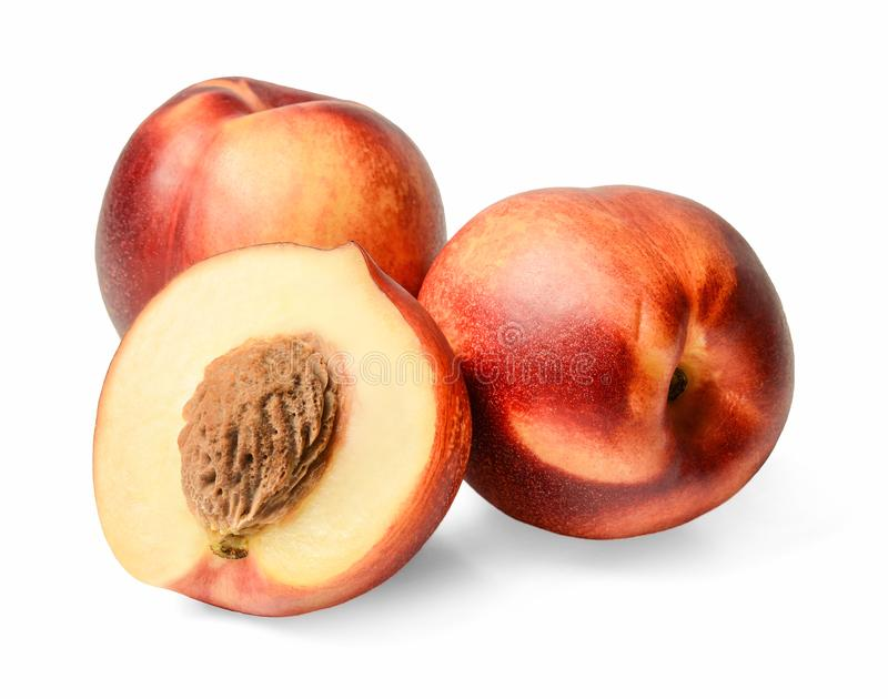 The composition of two whole and one half of nectarines. White isolated background. Close-up. Side view stock photography