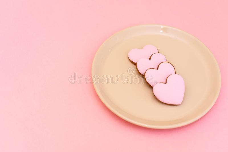 Composition Valentine`s Day. Ginger cookie in shape heart on pastel pink background. Valentine day concept, design royalty free stock images