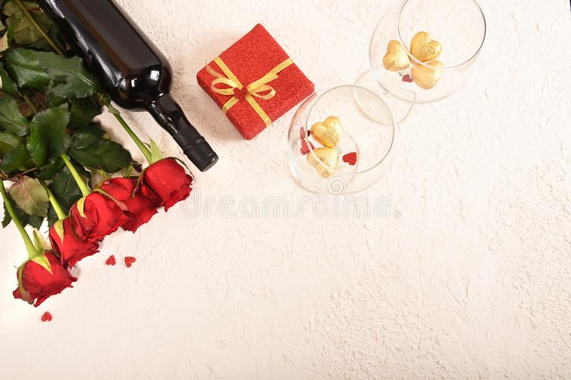 Composition for Valentine`s Day. Roses, gift, glasses and wine, red hearts. Top view. stock photos
