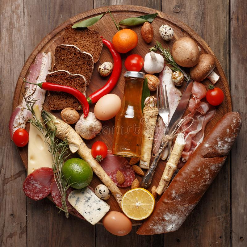 Composition of various foodstuffs on a wooden table. Top view royalty free stock photos