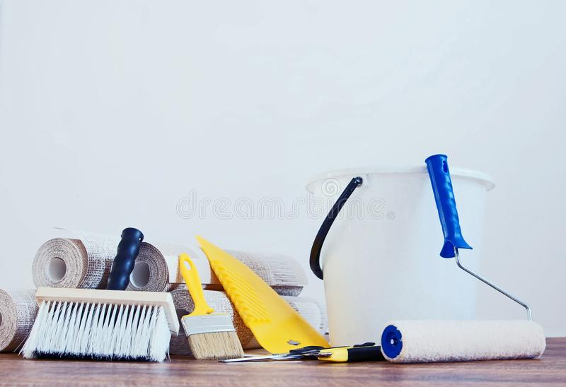 Composition with various tools for wallpapering and rolls of wallpaper. Against white empty wall stock image