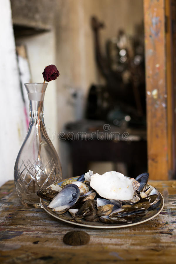 Composition of a vase, rose and a plate filled with clams stock photos