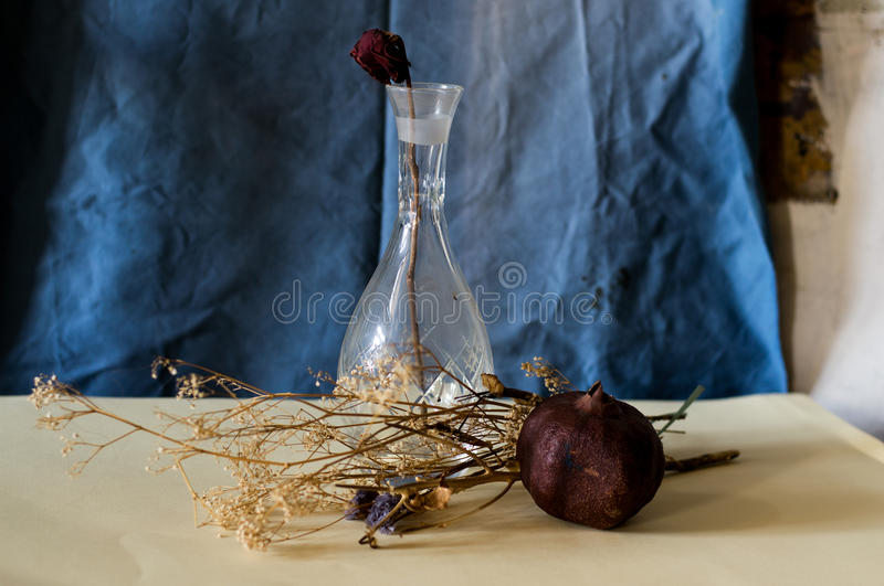 Composition of a vase, rose, pomegranate and withered flowers stock images