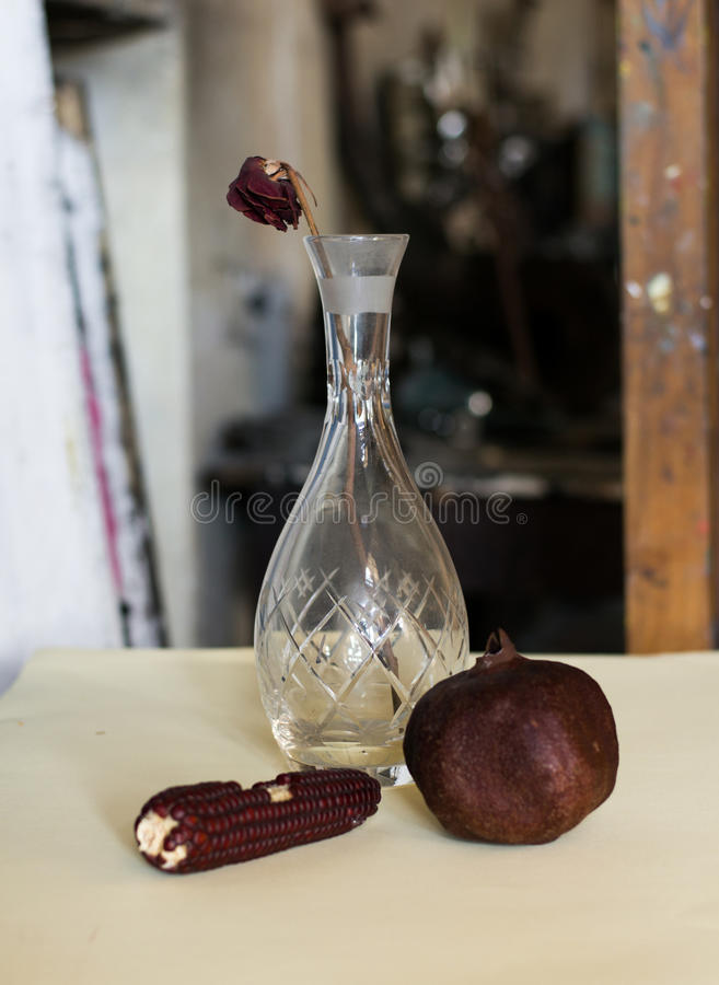 Composition of a vase, withered rose, pomegranate and a corn royalty free stock photos