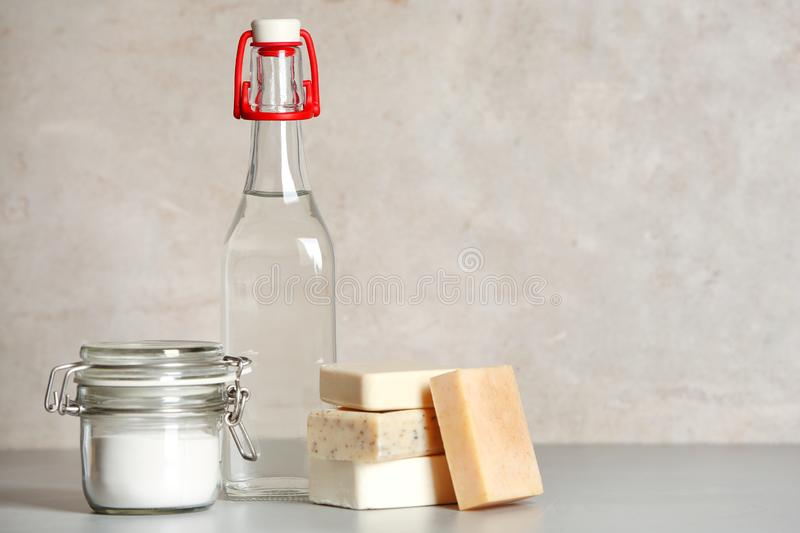 Composition with vinegar, baking soda and soap bars for cleaning on table. Space for text royalty free stock photos