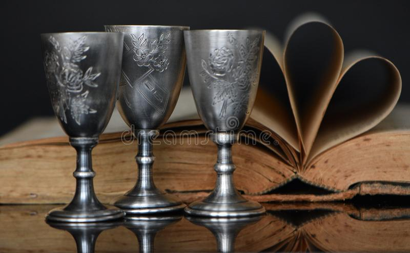 Still life of silver glasses and books. stock photos