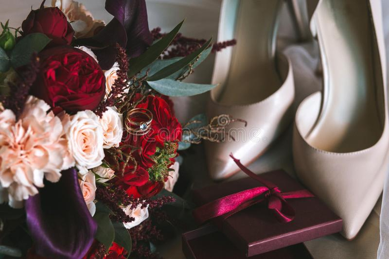 Composition from a wedding bouquet of white and red roses with gold rings with topaz, beige bride shoes and boxes. Composition from a wedding bouquet of white stock photos