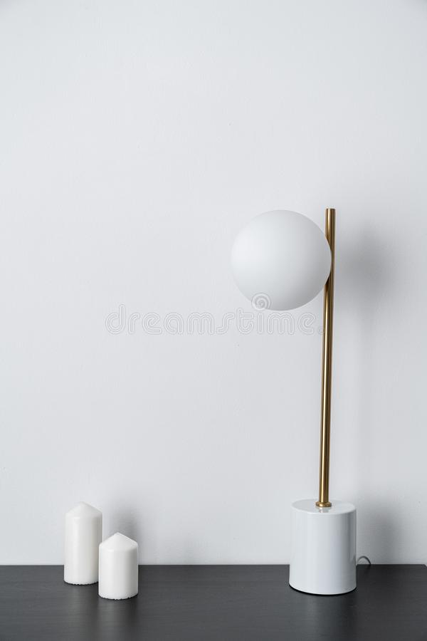 Composition of white candles and gold stylish table lamp in mid century modern design standing on black wooden top with white back royalty free stock photo