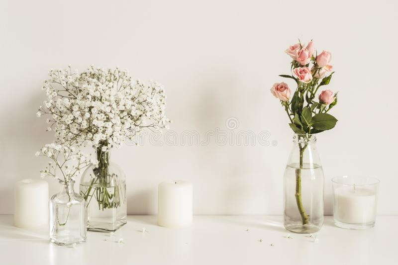Composition with white and pink flowers in glass bottles and candles on table wall background. Copy space for artwork royalty free stock images