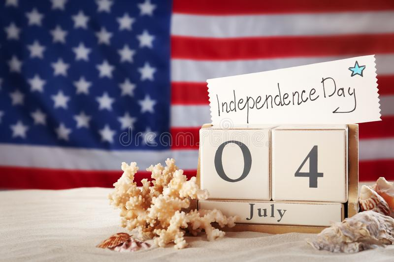 Composition with wooden calendar and card on sand against USA flag. Happy Independence Day. Composition with wooden calendar and card on sand against USA flag stock image