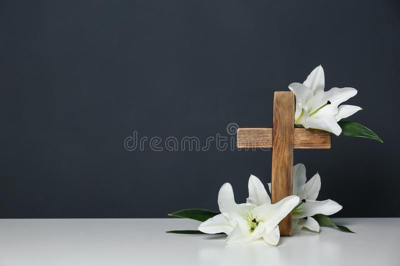 Composition with wooden cross and blossom lilies on table against color background. Space for text stock photo