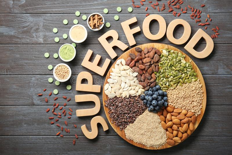 Composition with wooden letters and assortment of superfood products on grey table, royalty free stock photos