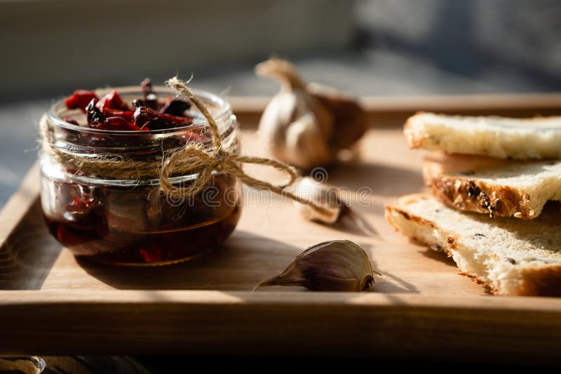 Still life with sun-dried tomatoes, garlic and bread on a sunny day. Composition on wooden tray with sun-dried tomatoes, garlic and dried bread. Vegetable royalty free stock photos