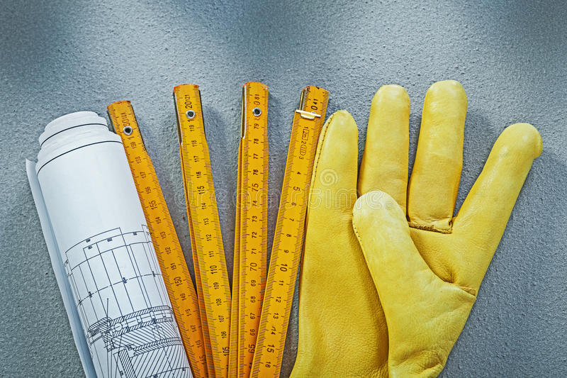 Composition of working gloves construction plans wooden meter on. Concrete background building concept stock images