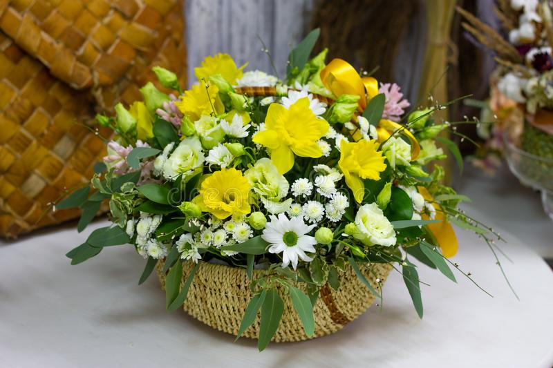 Composition with yellow daffodils in a basket floral background stock photo