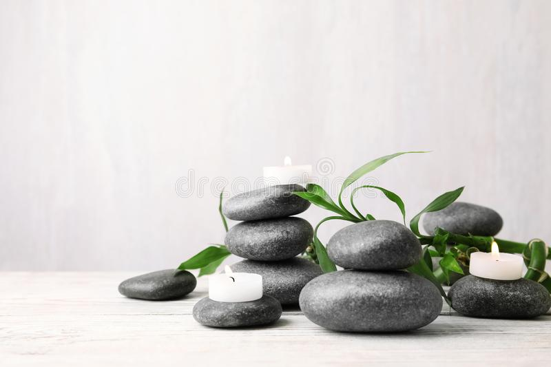 Composition with zen stones, bamboo and lighted candles on table against light background. Space for text stock image