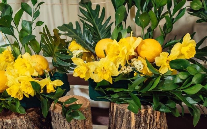 Compositions florales en mariage des jonquilles, de la verdure et des citrons jaunes images libres de droits