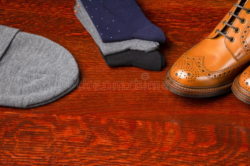 Compositions Made Up of Mens Fashionable Tanned Brogues. Footwear Compositions Made Up of Mens Fashionable Tanned Brogues Boots, Warm Hat and Batch of Socks Laid stock images