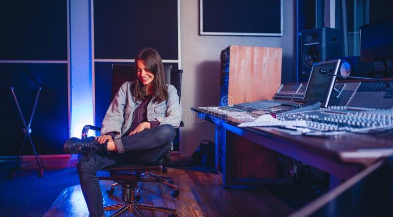 Compositor sonriente de la música de la mujer joven en el estudio de grabación imagen de archivo