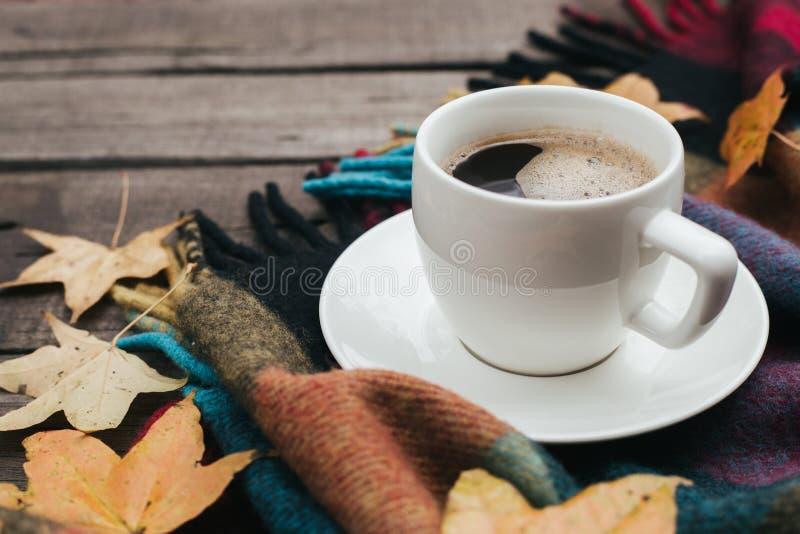 Composizione accogliente in autunno con le foglie del plaid e una tazza di caffè su vecchio fondo di legno d'annata immagini stock