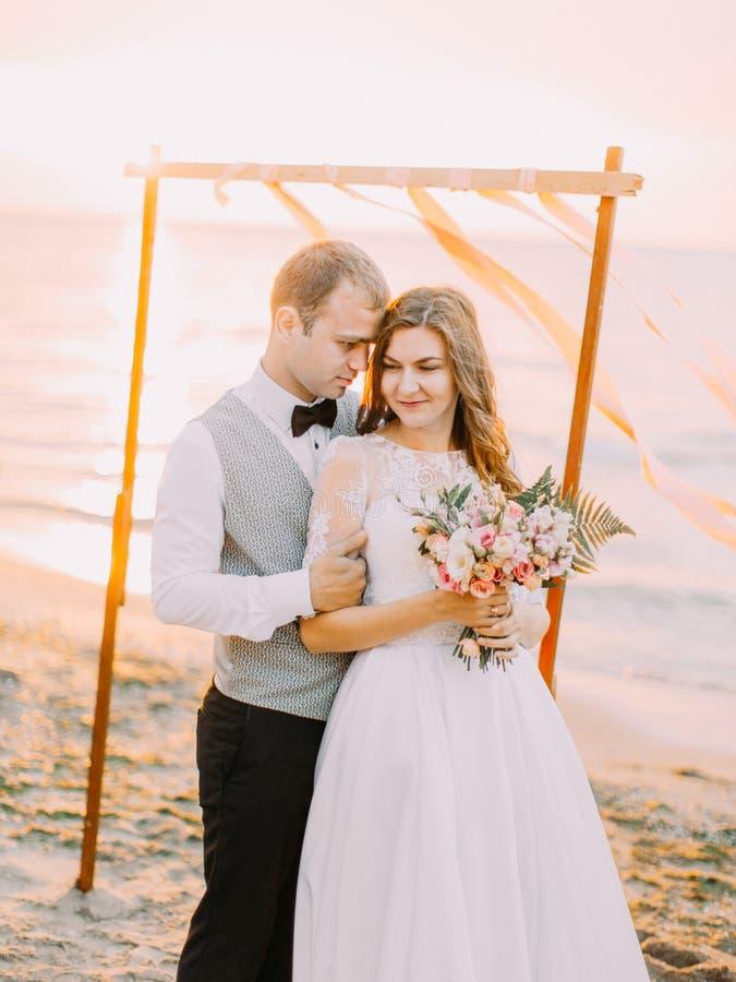 Composizione adorabile delle persone appena sposate che abbracciano sulla spiaggia durante il tramonto immagine stock