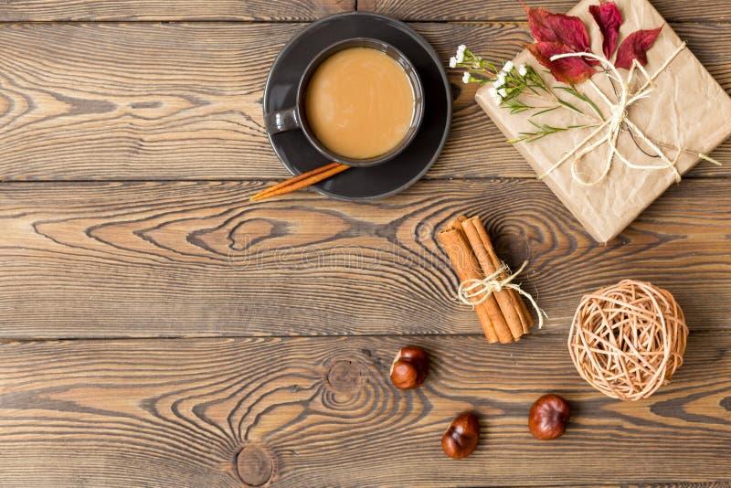Composizione in autunno Caffè con latte, il regalo, le foglie di autunno, i bastoni di cannella e le castagne su fondo di legno fotografia stock libera da diritti