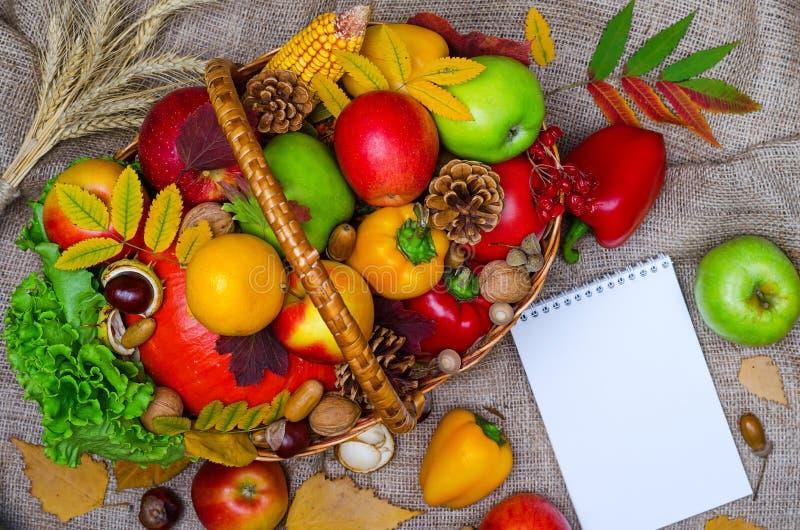 Composizione in autunno: canestro di vimini con la frutta e la cima delle verdure fotografia stock