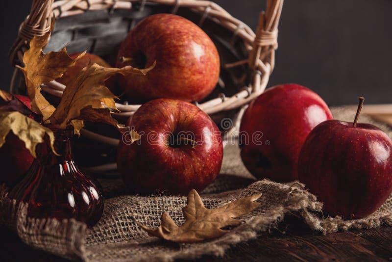 Composizione in autunno con le mele e la cannella rosse fresche in un canestro di legno su fondo di legno rustico Mele e cannella fotografia stock