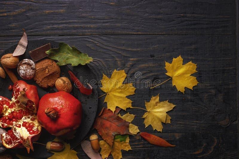 Composizione in autunno Melograno con i dadi, le spezie e le foglie asciutte su una tavola di legno scura Vista superiore Copi lo fotografie stock libere da diritti