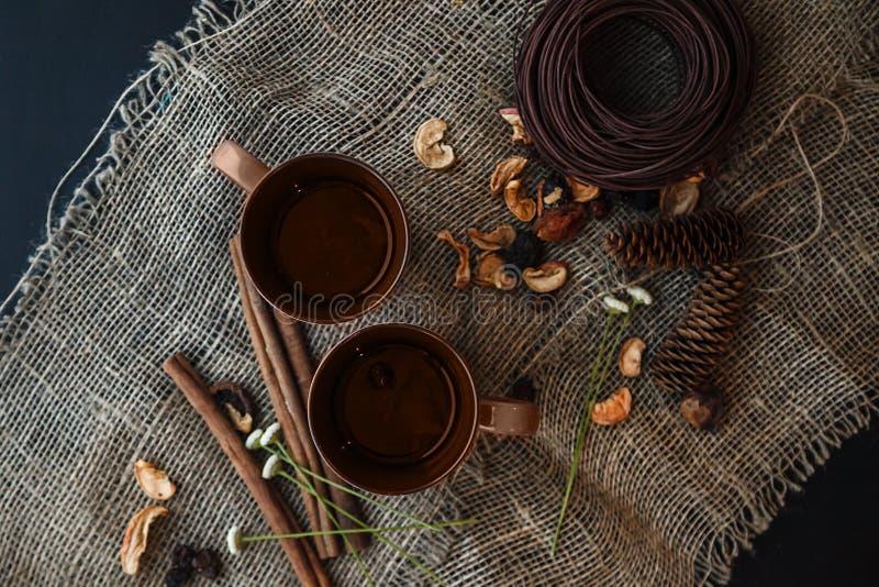 Composizione in autunno: 2 tazze, cannella, pinecones sul Cl della tela fotografie stock libere da diritti