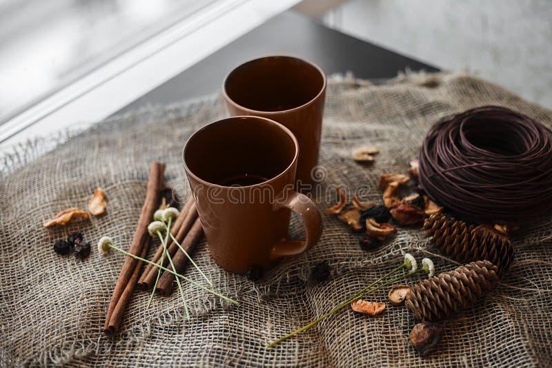 Composizione in autunno: 2 tazze, cannella, pinecones sulla tela fotografia stock libera da diritti