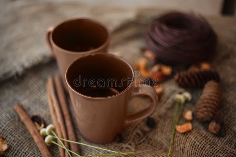 Composizione in autunno: 2 tazze, cannella, pinecones sulla tela immagine stock