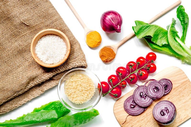 Composizione casalinga negli ingredienti della paella con riso, pomodoro, cipolla sulla vista superiore del fondo bianco della ta fotografie stock libere da diritti