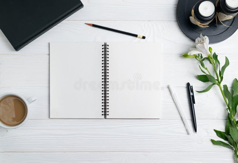 Composizione con i fiori stazionari del caffè della matita della penna del taccuino di istruzione dell'ufficio immagini stock