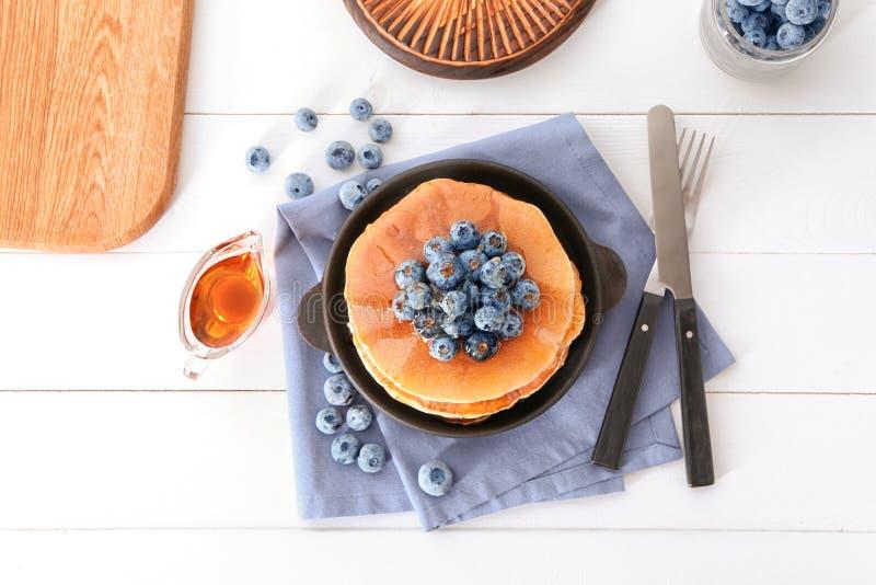 Composizione con i pancake ed i mirtilli saporiti sulla tavola di legno bianca immagini stock