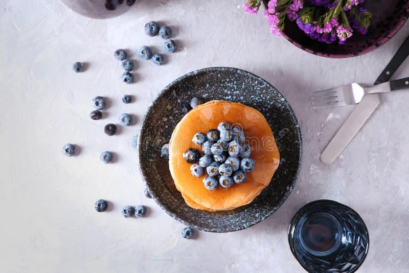 Composizione con i pancake ed i mirtilli saporiti sulla tavola leggera immagini stock libere da diritti