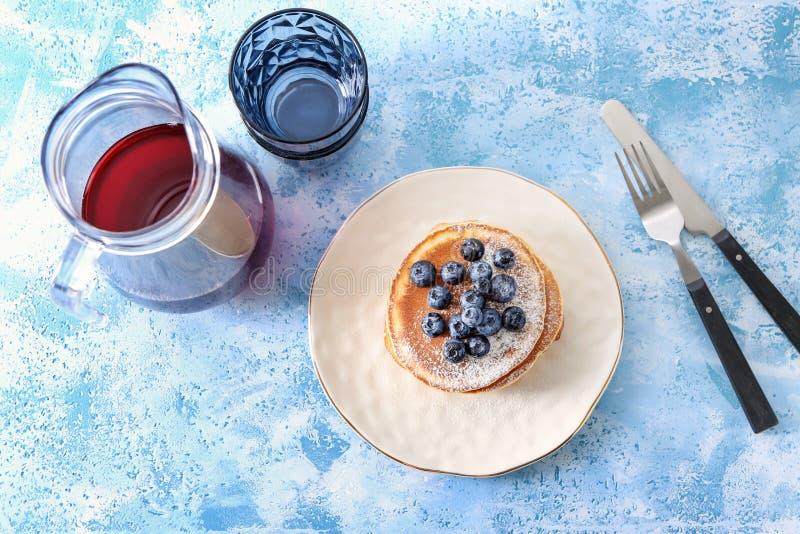 Composizione con i pancake, i mirtilli e la brocca saporiti di bevanda sulla tavola fotografia stock libera da diritti