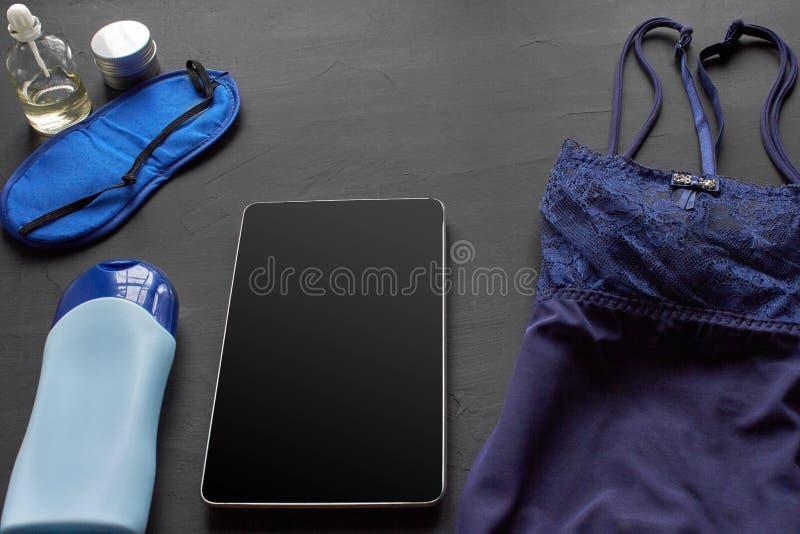 Composizione con i prodotti cosmetici di cura di pelle senza etichetta e biancheria bianca su un fondo da tavolino nero fotografia stock