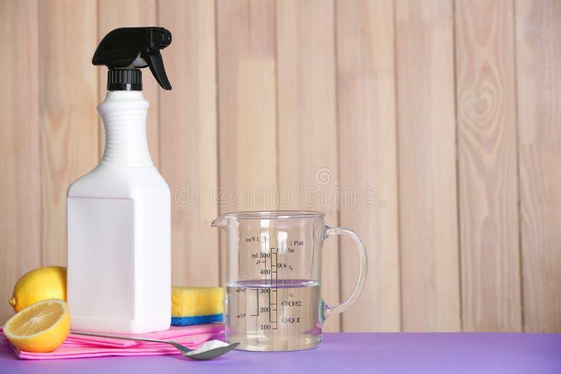 Composizione con i rifornimenti di pulizia e dell'all'aceto sulla tavola immagini stock libere da diritti