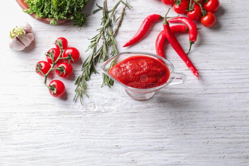 Composizione con il crogiolo di sugo di salsa al pomodoro deliziosa sulla tavola di legno immagini stock